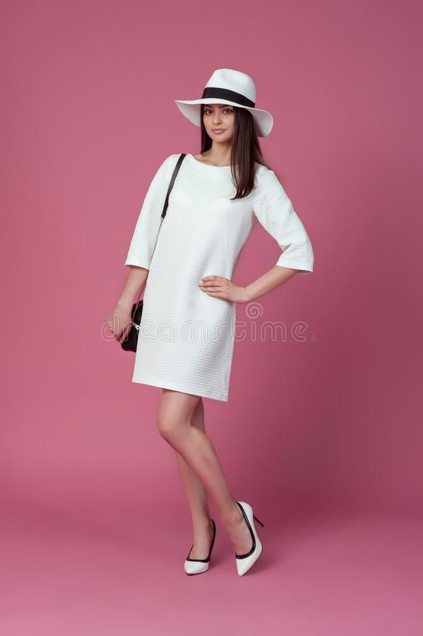 Piękna młoda kobieta w eleganckiej biel sukni i lato kapeluszu Dziewczyna pozuje na różowym tle bedsheet moda kłaść fotografii uw obrazy royalty free