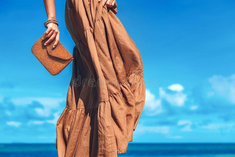 Piękna młoda kobieta w eleganckiej sukni z sprzęgłem na plaży obraz royalty free