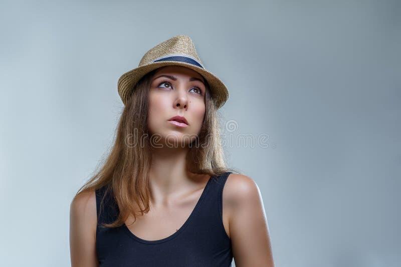 Piękna młoda kobieta w kapeluszu i czarnej koszula jest przyglądająca w górę odosobnionego na szarym tle w pracownianym zakończen fotografia stock