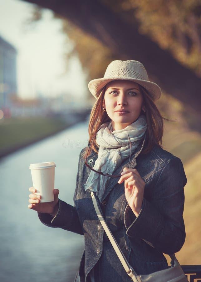 Piękna młoda kobieta w kapeluszu i szaliku z filiżanką kawy obrazy royalty free