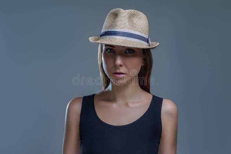 Piękna młoda kobieta w koszula odizolowywających na szarym tle w studiu czarnym moda kapeluszu i fotografia royalty free