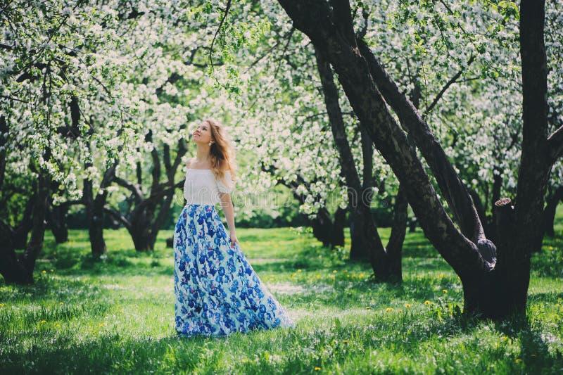 Piękna młoda kobieta w kwiecistym maksim spódnicowym odprowadzeniu w wiośnie obrazy stock