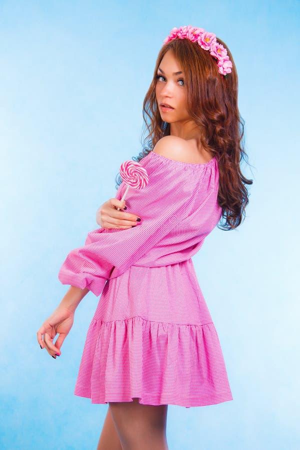 Piękna młoda kobieta w menchii ubraniach z wiankiem i cukierkiem fotografia stock