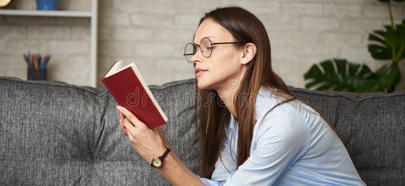 Piękna młoda kobieta w okularach czyta książkę obraz stock