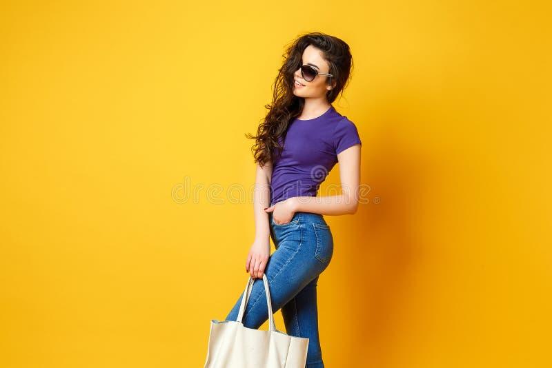 Piękna młoda kobieta w okularach przeciwsłonecznych, purpurowa koszula, niebiescy dżinsy pozuje z torbą na żółtym tle fotografia stock