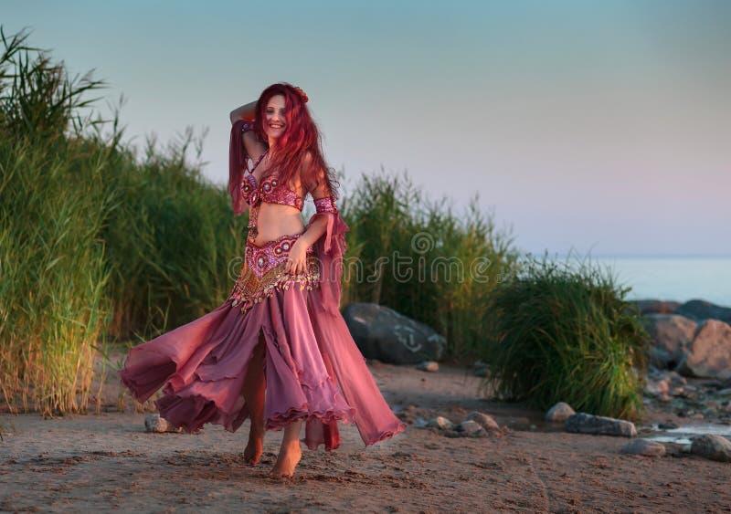Piękna młoda kobieta w Orientalnym tana kostiumu morzem obraz stock