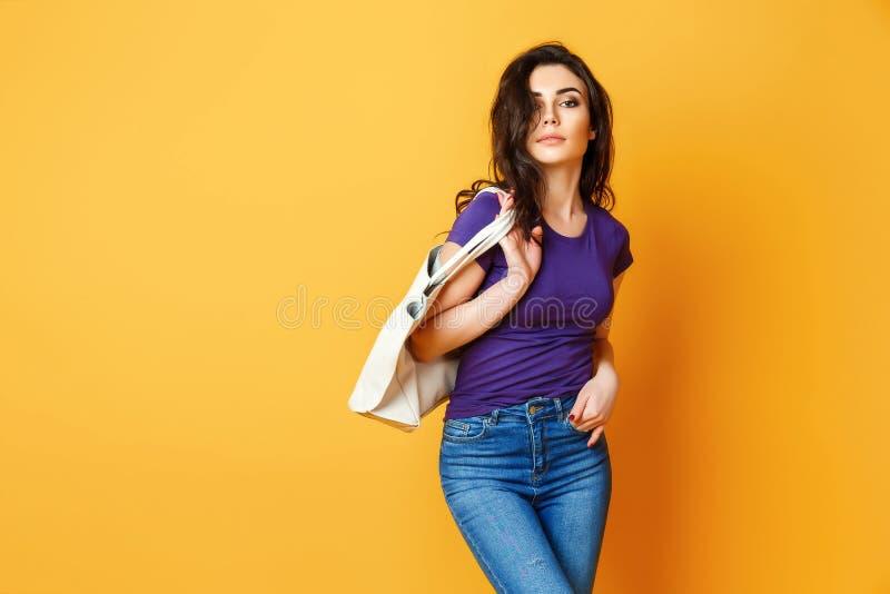 Piękna młoda kobieta w purpurowej koszula, niebiescy dżinsy pozuje z torbą na żółtym tle obraz royalty free