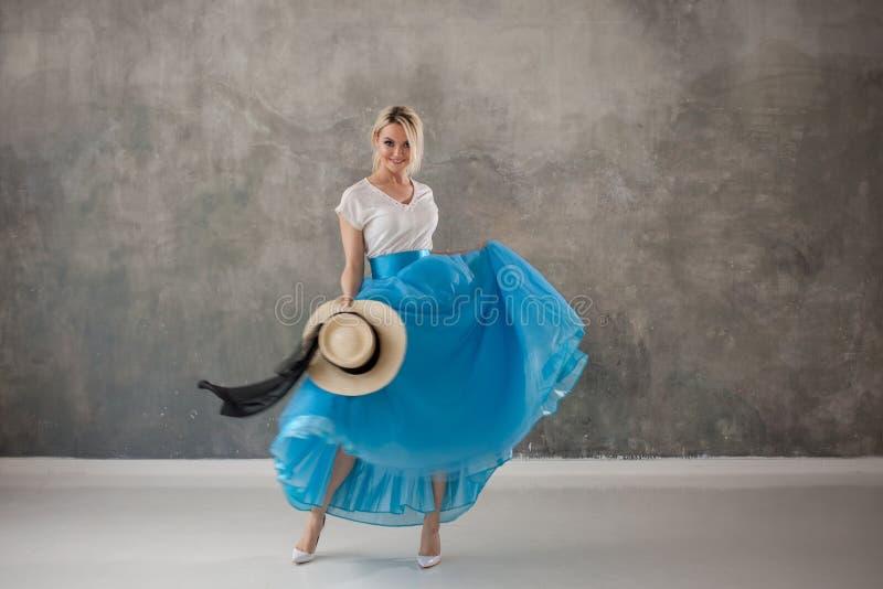 Piękna młoda kobieta w spódnicie, kłębieniu i tanu luksusowych błękita, Lato styl, słomiany kapelusz z czarnym faborkiem zdjęcie stock