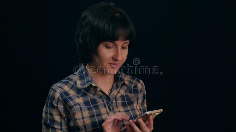 Piękna młoda kobieta w szkockiej kraty bluzce używać smartphone na czarnym tle - 2 fotografia stock
