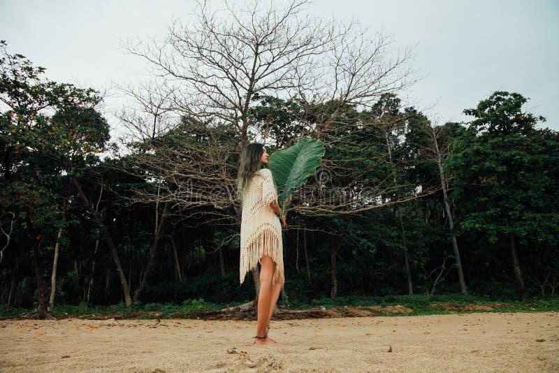 Piękna młoda kobieta w tunice na plaży z wielkiego liścia tropikalnym drzewkiem palmowym obraz royalty free