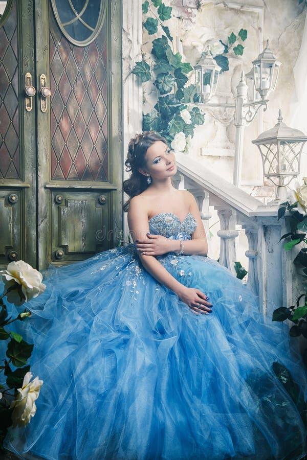 Piękna młoda kobieta w wspaniałego błękita długiej sukni jak Kopciuszek z perfect makijażem i włosianym stylem obraz royalty free