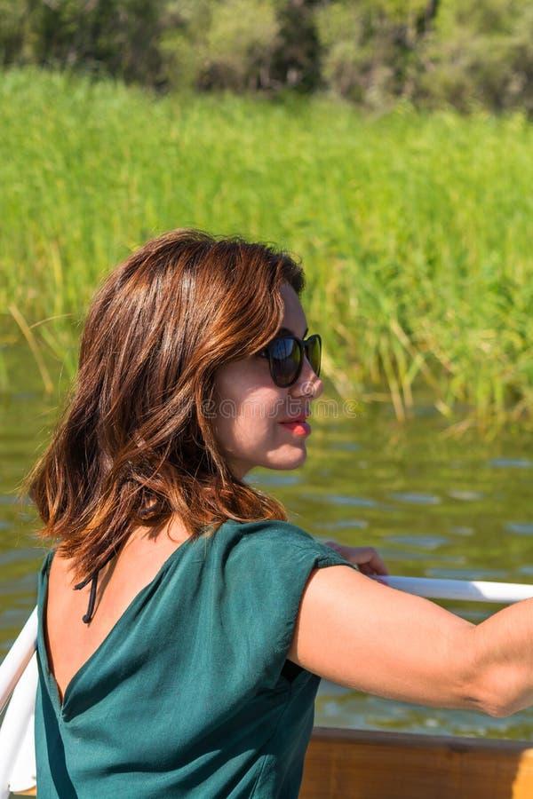 Piękna młoda kobieta w zielonej bluzce, okulary przeciwsłoneczni siedzi na pokładzie łódź zdjęcia royalty free