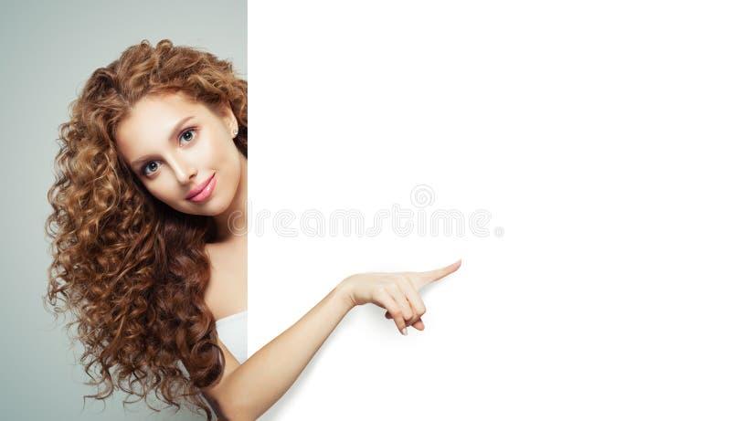 Piękna młoda kobieta wskazuje pustego papierowego sztandaru tło i pokazuje bielowi fotografia stock