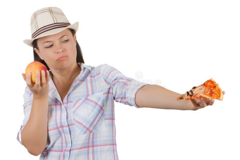 Piękna młoda kobieta Wybiera plasterek pizza lub Świeża brzoskwinia fotografia stock