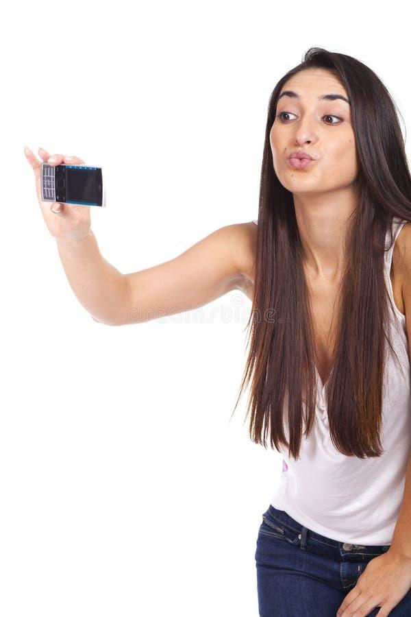 Piękna młoda kobieta wysyła buziaka telefonem zdjęcie stock