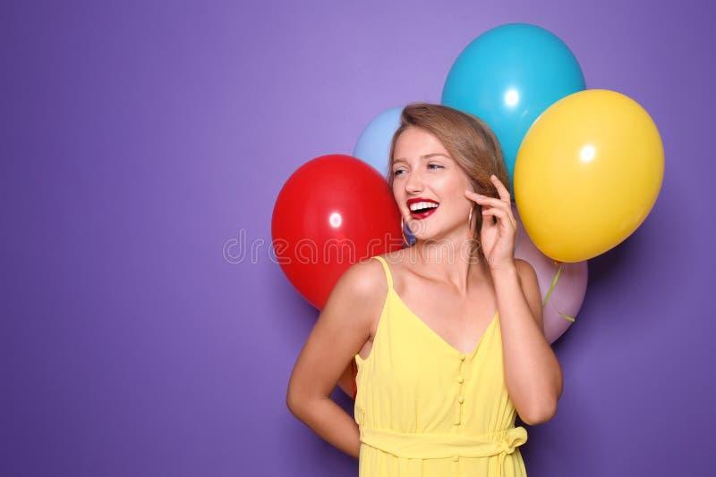 Piękna młoda kobieta z balonami na koloru tle zdjęcie royalty free