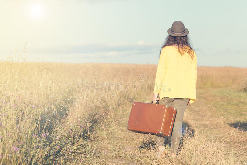 Piękna młoda kobieta z czarnym kapeluszem niesie brown rocznik walizkę w śródpolnej drodze podczas lato zmierzchu widok z powrote obrazy stock
