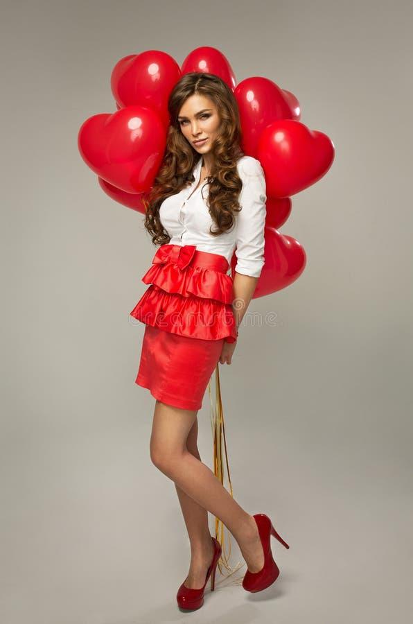 Piękna młoda kobieta z czerwień balonu kierowym kształtem dla valentine obraz stock
