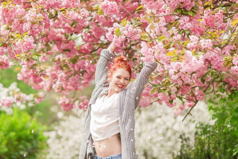 Piękna młoda kobieta z czerwony włosianym mieć zabawy pozycję w czereśniowego okwitnięcia drzewie obrazy stock