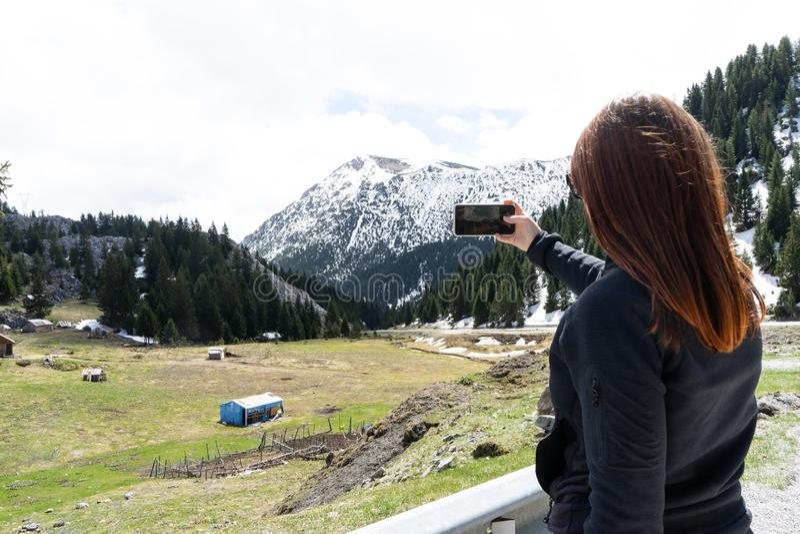 piękna młoda kobieta z czerwonym fotografem robi zdjęcie górskiego krajobrazu podczas podróży obrazy royalty free
