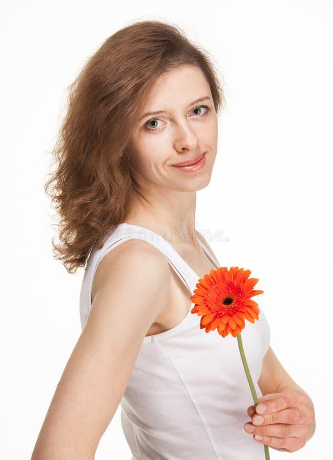 Piękna młoda kobieta z czerwonym gerber kwiatem zdjęcie stock