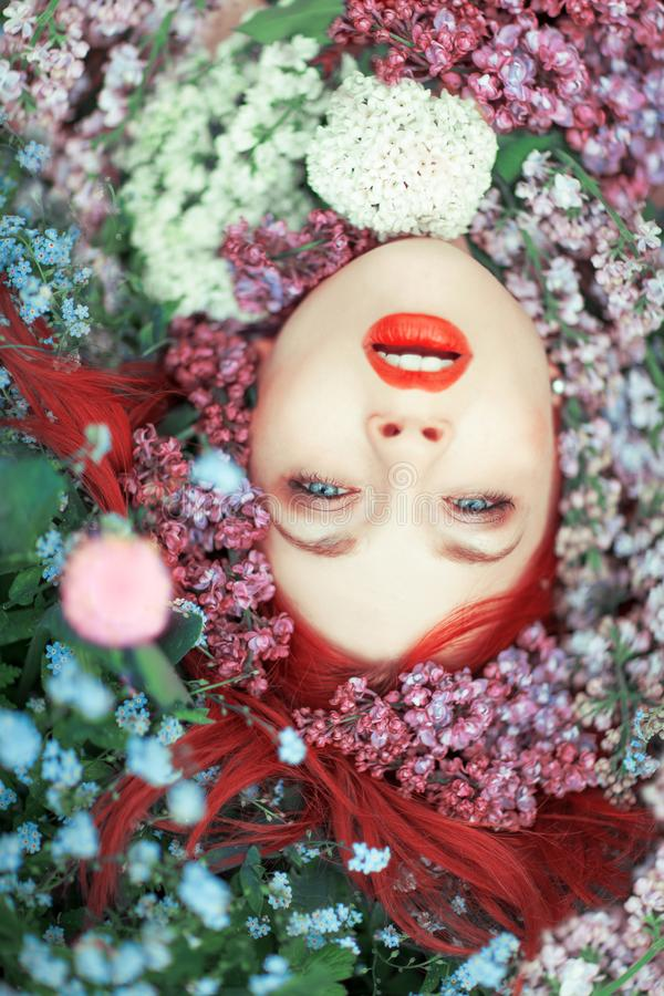 Piękna młoda kobieta z czerwonym włosianym lying on the beach w kolorowych kwiatach, zamyka w górę twarzy zdjęcia royalty free