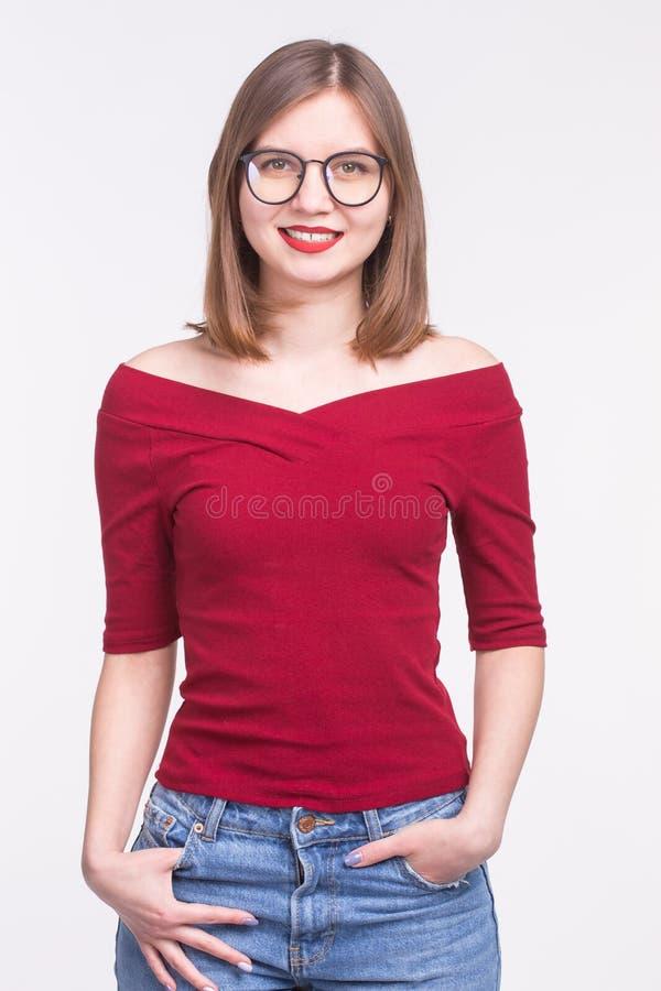 Piękna młoda kobieta z czerwonymi wargami w szkłach pozuje w czerwonym wierzchołku nad białym tłem fotografia royalty free