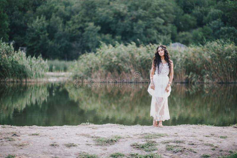 Piękna młoda kobieta z długim kędzierzawym włosy ubierał w boho stylu smokingowy pozować blisko jeziora obrazy stock
