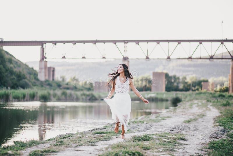 Piękna młoda kobieta z długim kędzierzawym włosy ubierał w boho stylu smokingowy pozować blisko jeziora zdjęcie royalty free