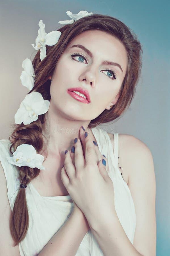 Piękna młoda kobieta z delikatnymi kwiatami w ich włosy obrazy stock