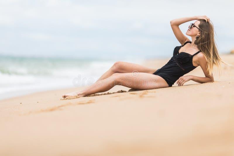 Piękna młoda kobieta z doskonalić ciało łgarskim puszkiem na plaży, garbnikujący na miejscowości nadmorskiej, cieszy się wakacje zdjęcie royalty free