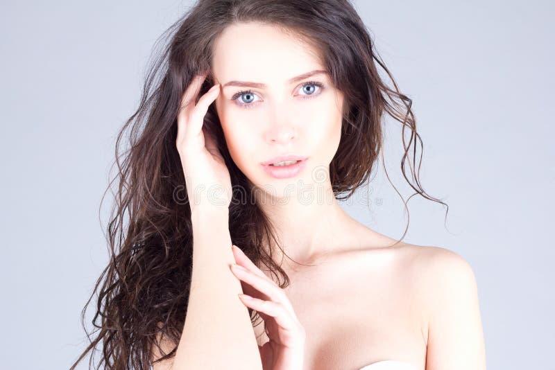 Piękna młoda kobieta z dużymi niebieskimi oczami i kędzierzawego włosy macaniem przewodzi piękna twarz kobiety zdjęcie royalty free