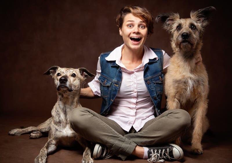 Piękna młoda kobieta z dwa śmiesznymi psami na ciemnym tle zdjęcia royalty free