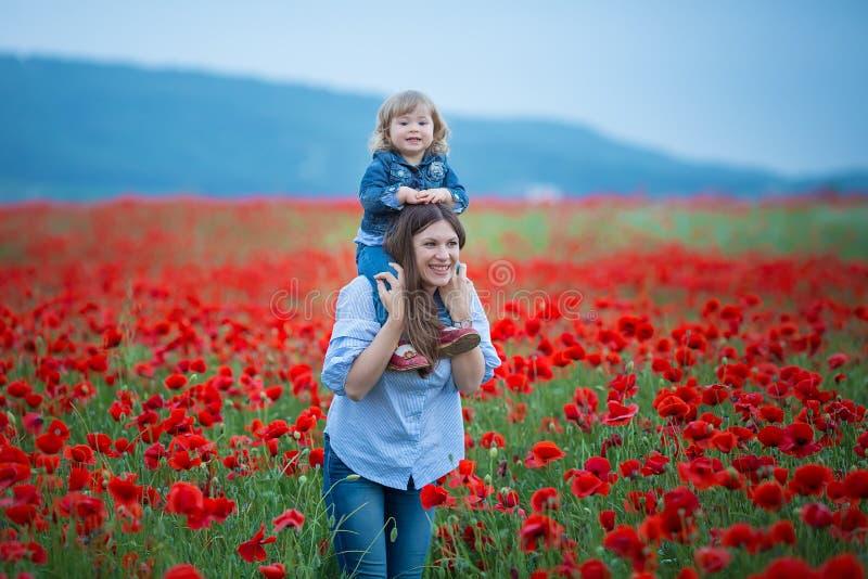Piękna młoda kobieta z dziecko dziewczyną w maczka polu szczęśliwy rodzinny mieć zabawę w naturze plenerowy portret w maczkach ma obrazy royalty free