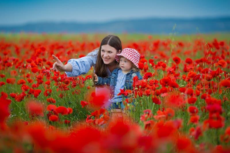 Piękna młoda kobieta z dziecko dziewczyną w maczka polu szczęśliwy rodzinny mieć zabawę w naturze plenerowy portret w maczkach ma zdjęcie stock