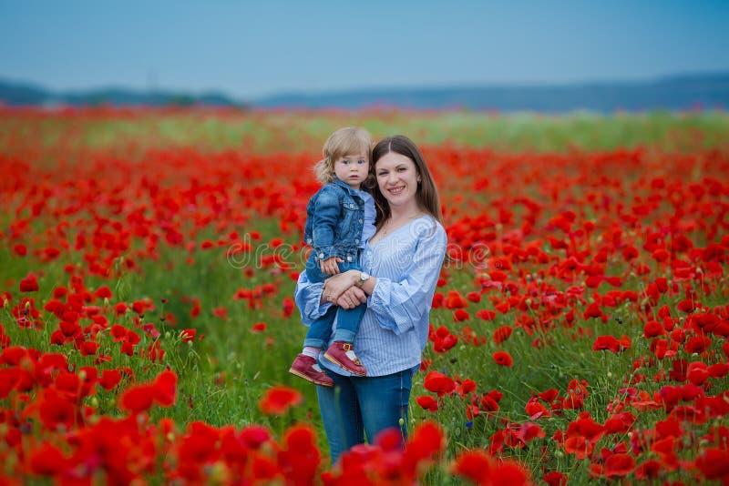 Piękna młoda kobieta z dziecko dziewczyną w maczka polu szczęśliwy rodzinny mieć zabawę w naturze plenerowy portret w maczkach ma obraz stock