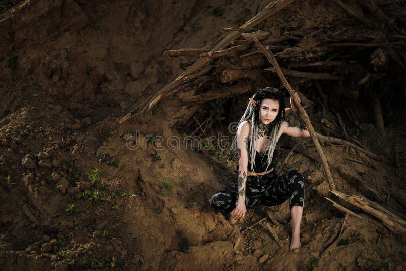Piękna młoda kobieta z elfów ucho dreadlocks i etniczny poncho z malującą twarzą, Pozować przeciw piaskowatej karierze obraz royalty free