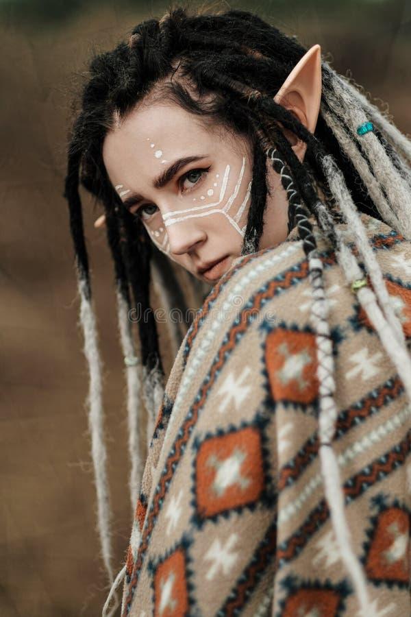 Piękna młoda kobieta z elfów ucho dreadlocks i etniczny poncho z malującą twarzą, Pozować przeciw piaskowatej karierze obrazy royalty free