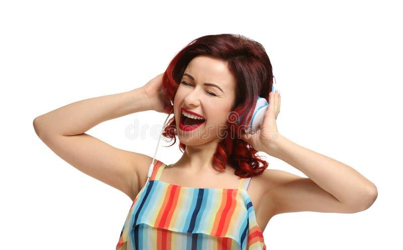 Piękna młoda kobieta z farbującą kędzierzawego włosy słuchającą muzyką zdjęcie stock