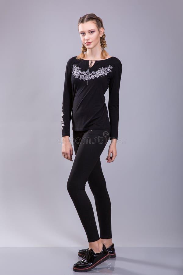 Piękna młoda kobieta z fryzur pigtails i wieczór makijaż ubieraliśmy w czarna ciasna broderia, spodniach lub bluzka i obrazy stock
