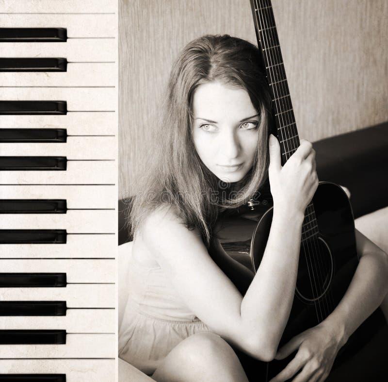 Piękna młoda kobieta z gitarą, pianino zdjęcie stock