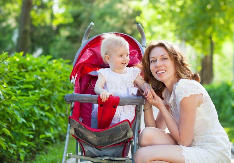 Piękna młoda kobieta z jej dzieckiem w dziecko frachcie fotografia stock