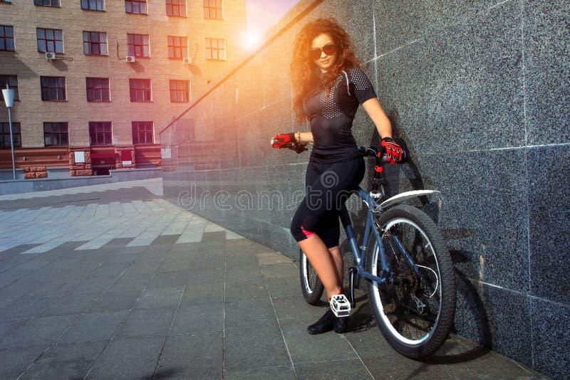 Piękna młoda kobieta z kędzierzawym czerwonym włosy na bicyklu obrazy royalty free