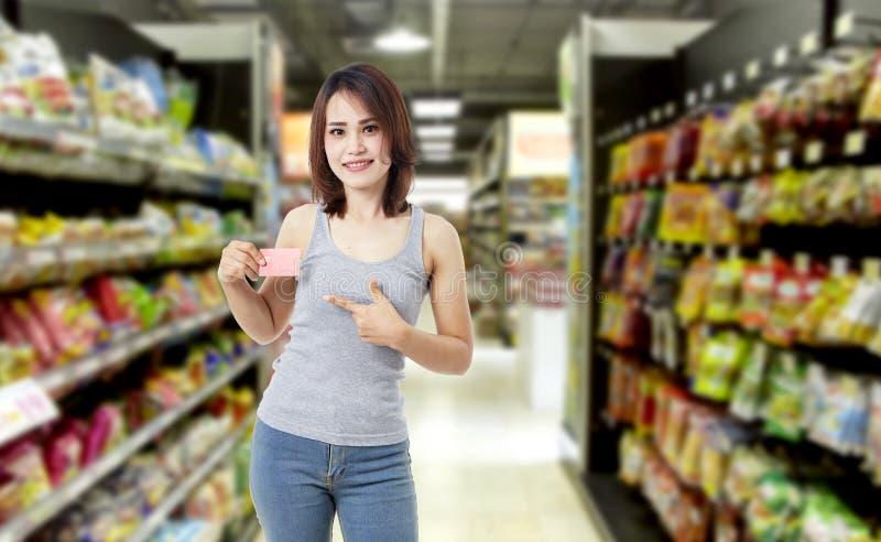 Piękna młoda kobieta z kartą kredytową w supermarkecie zdjęcie royalty free
