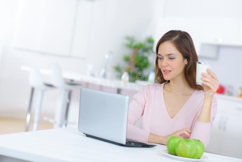 Piękna młoda kobieta z kawowym używa laptopem w kuchni obraz stock