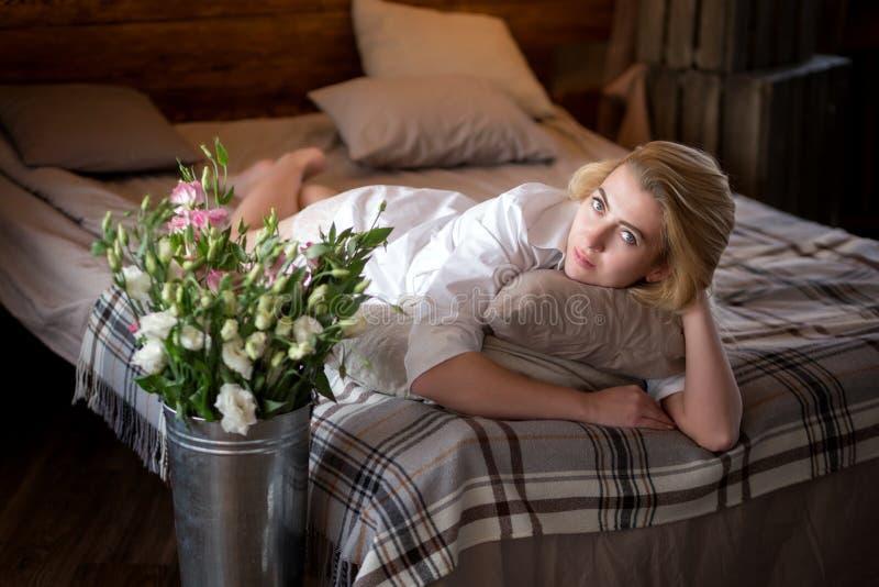 Piękna młoda kobieta z kwiatami na łóżku obrazy stock