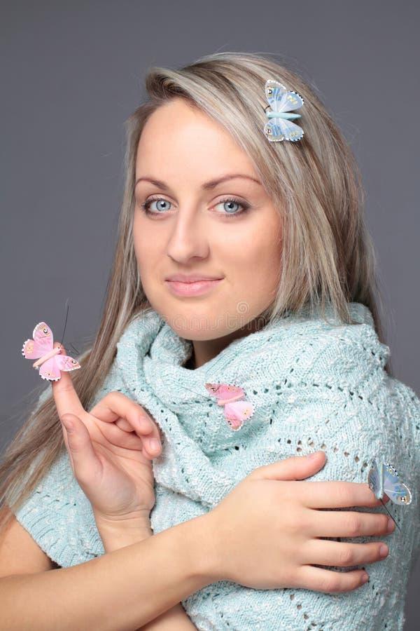 Piękna młoda kobieta z motylami w błękitnych szumowinach obrazy stock