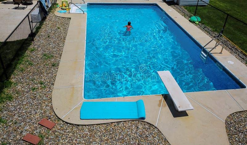 Piękna młoda kobieta z nadmuchiwanym ringowym relaksuje błękitnym pływackim basenem fotografia royalty free