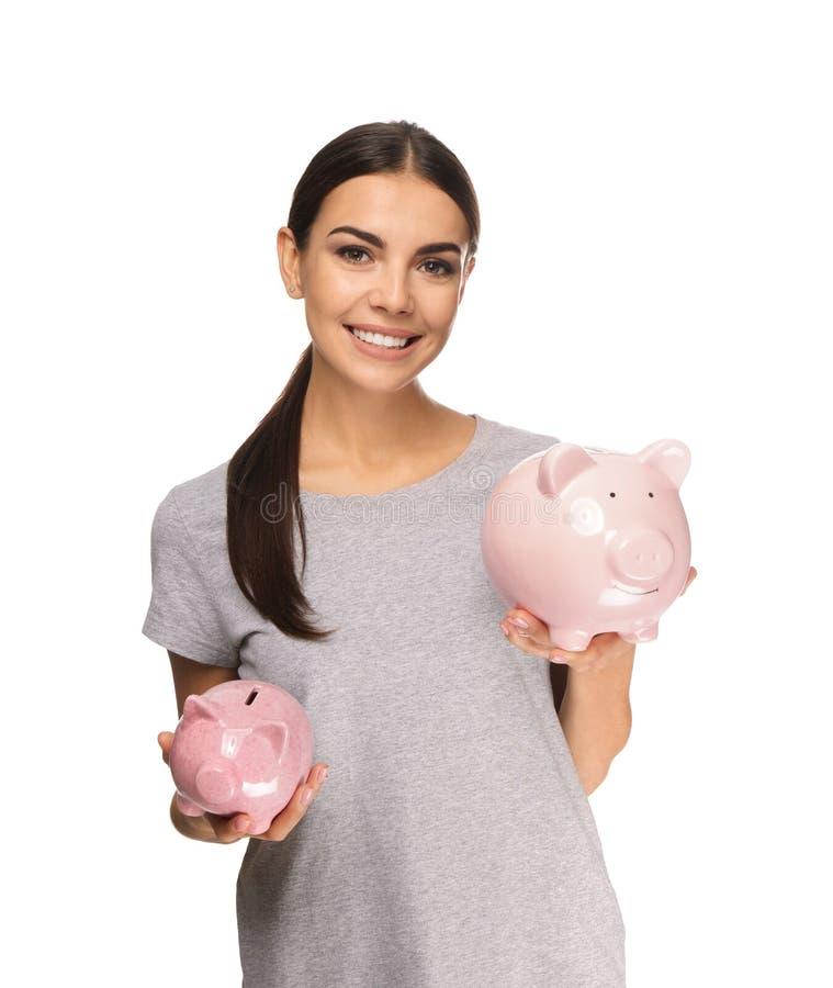 Piękna młoda kobieta z prosiątko bankami na białym tle fotografia royalty free