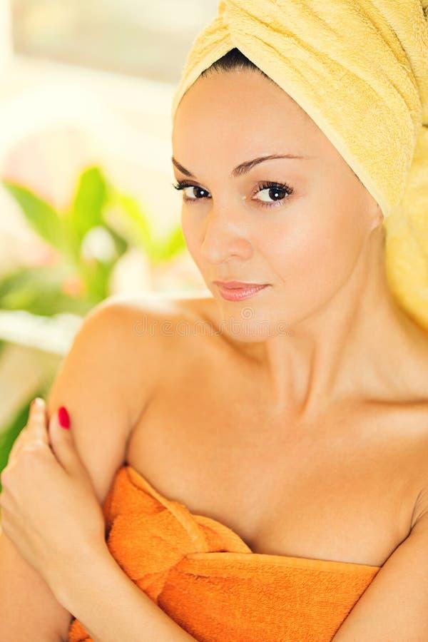 Piękna młoda kobieta z ręcznikiem na głowie zdjęcie stock